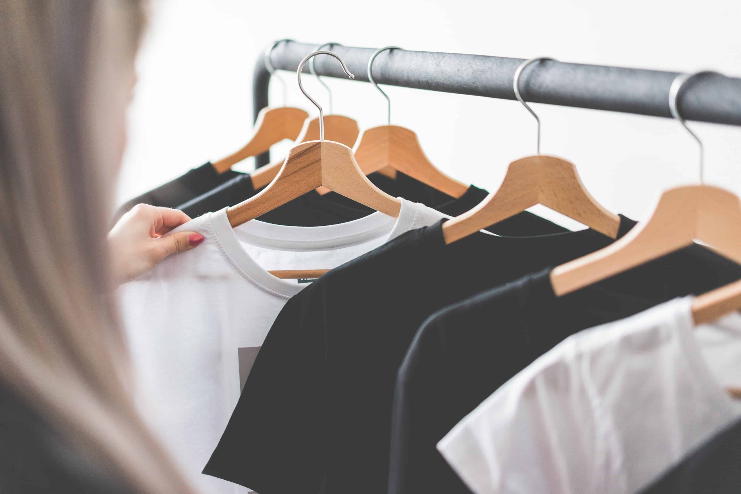 Woman choosing t shirts during clothing shopping at apparel store picjumbo com scaled