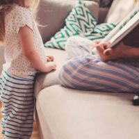 Pregnant mother reading to child about becoming big sister