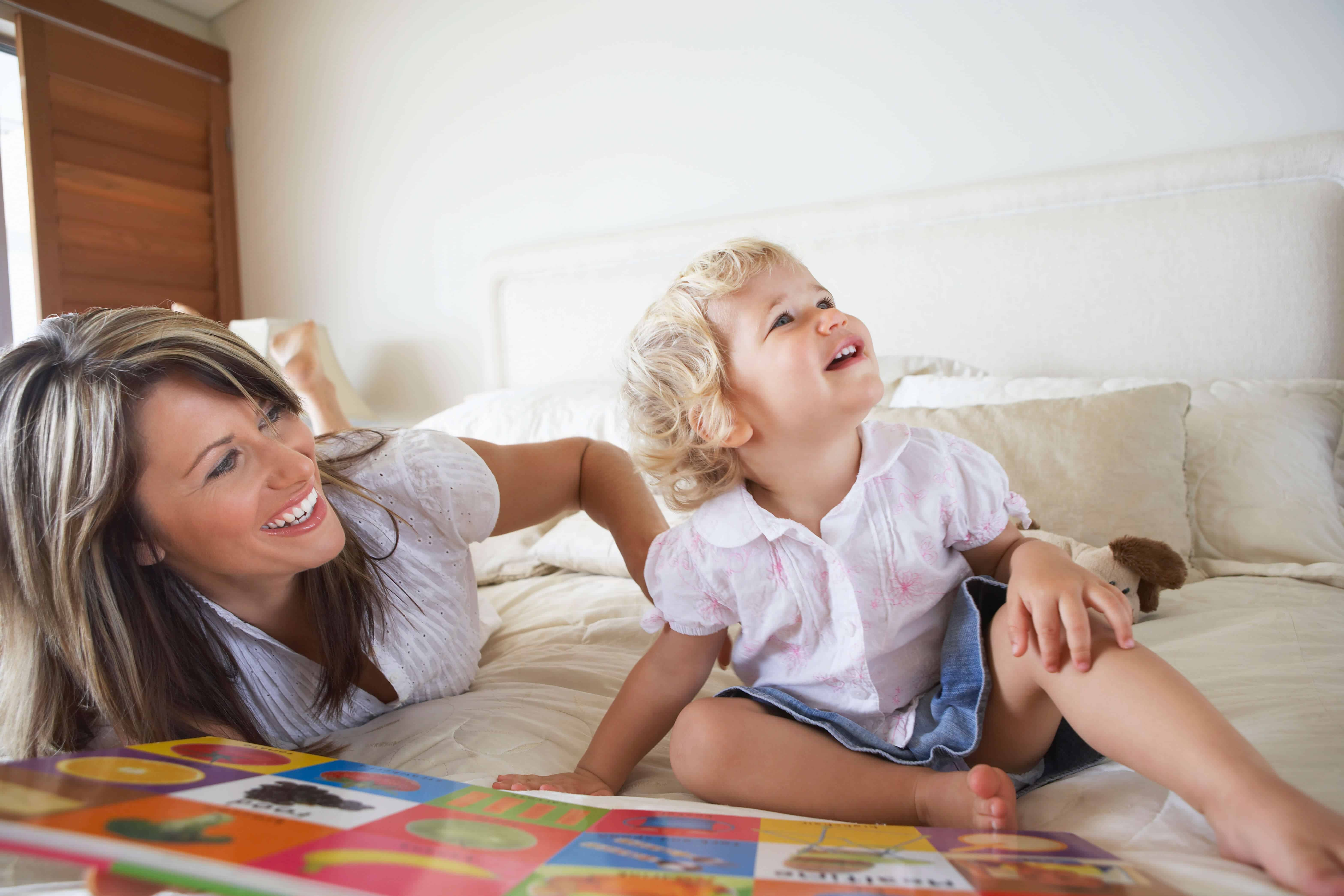 Toddler reading with mother on bed