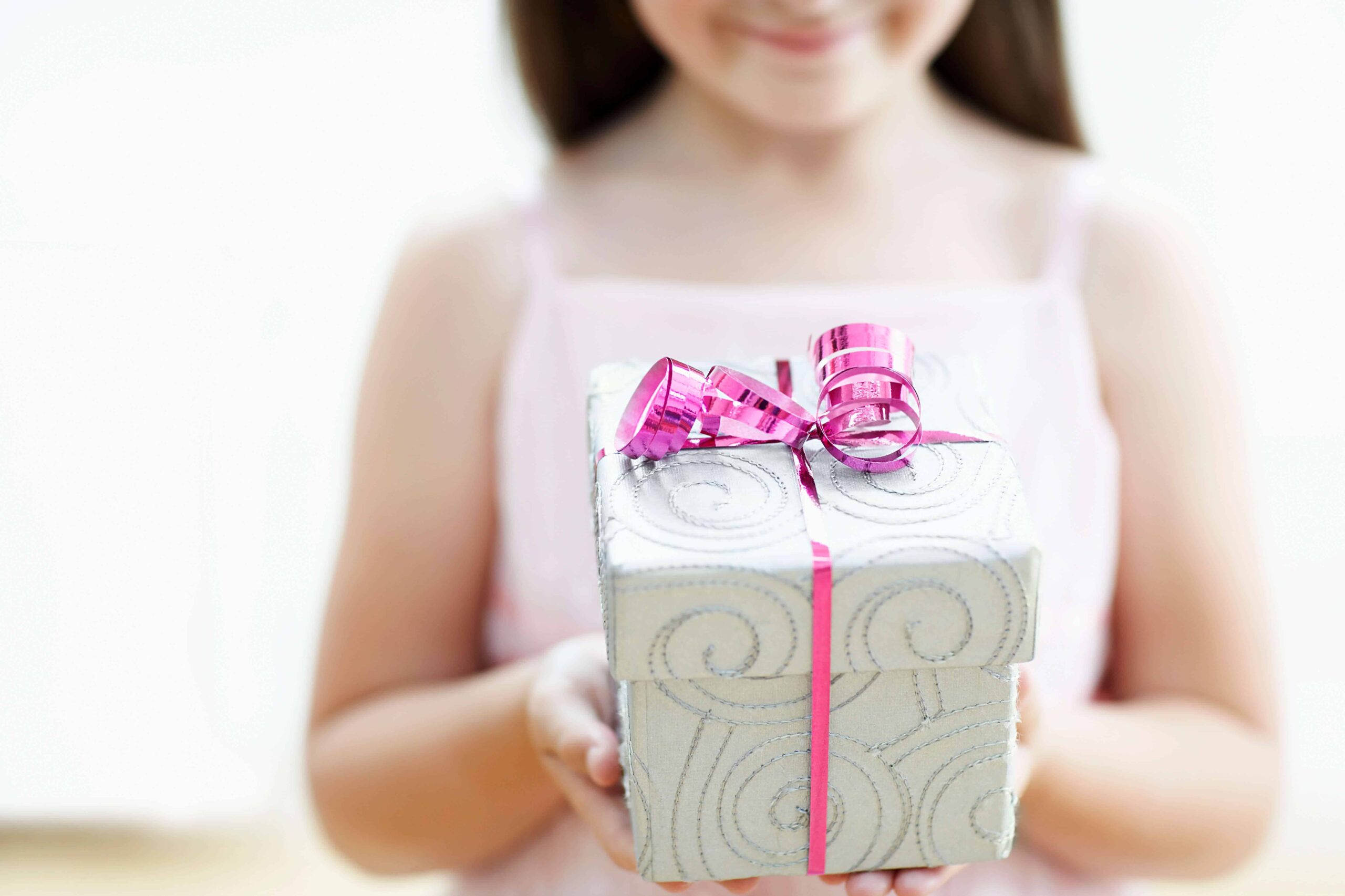 Non-toy gift ideas for kids girl holding gift box