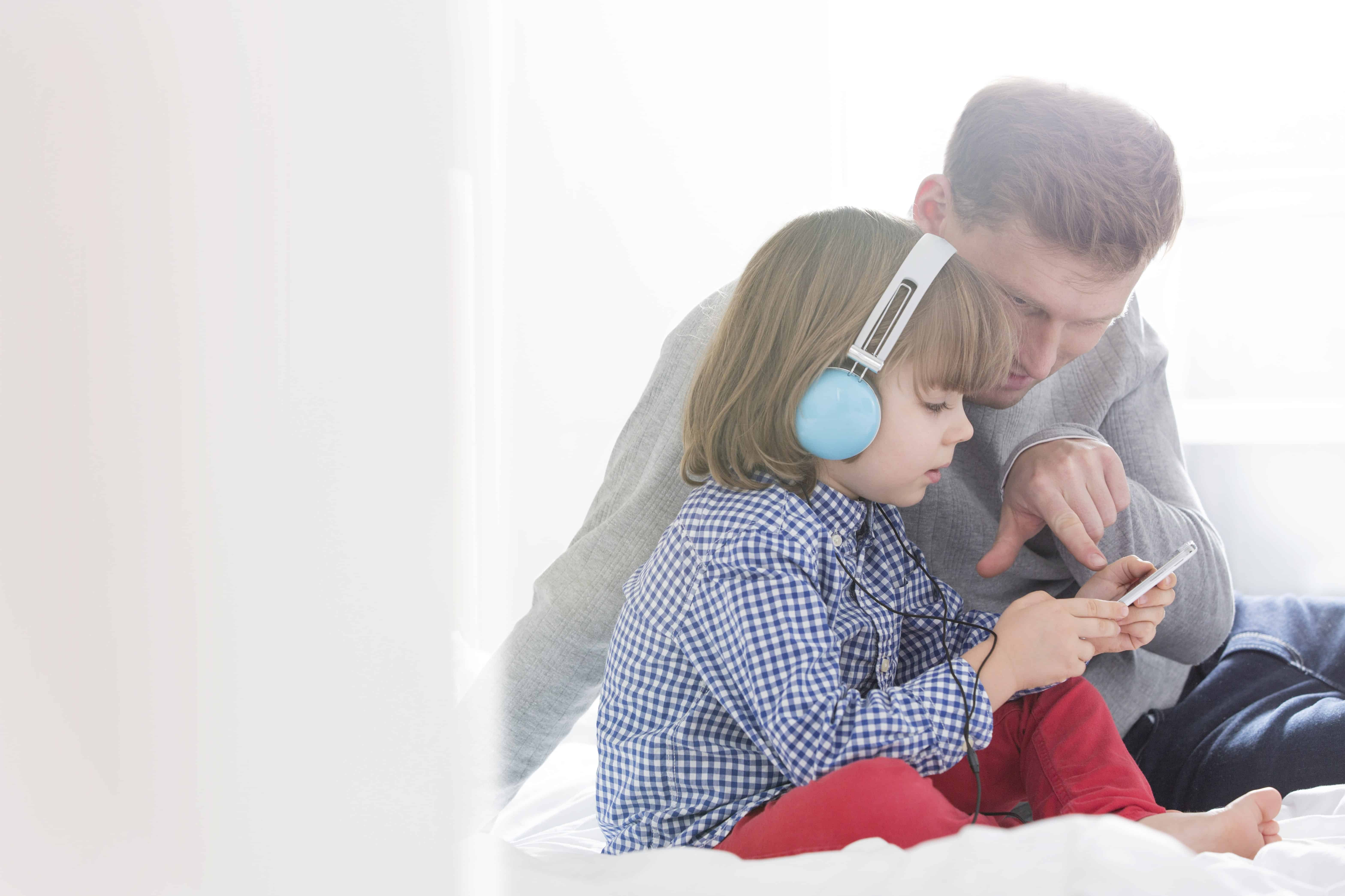 Child with headphones listening to music with father