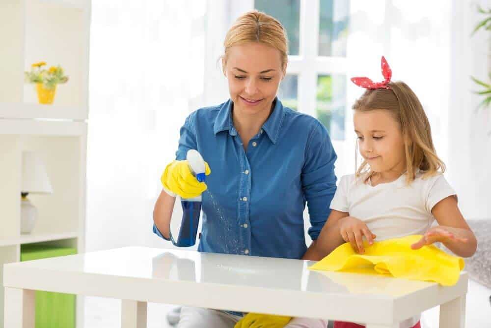 Mother teaching child how to clean bench