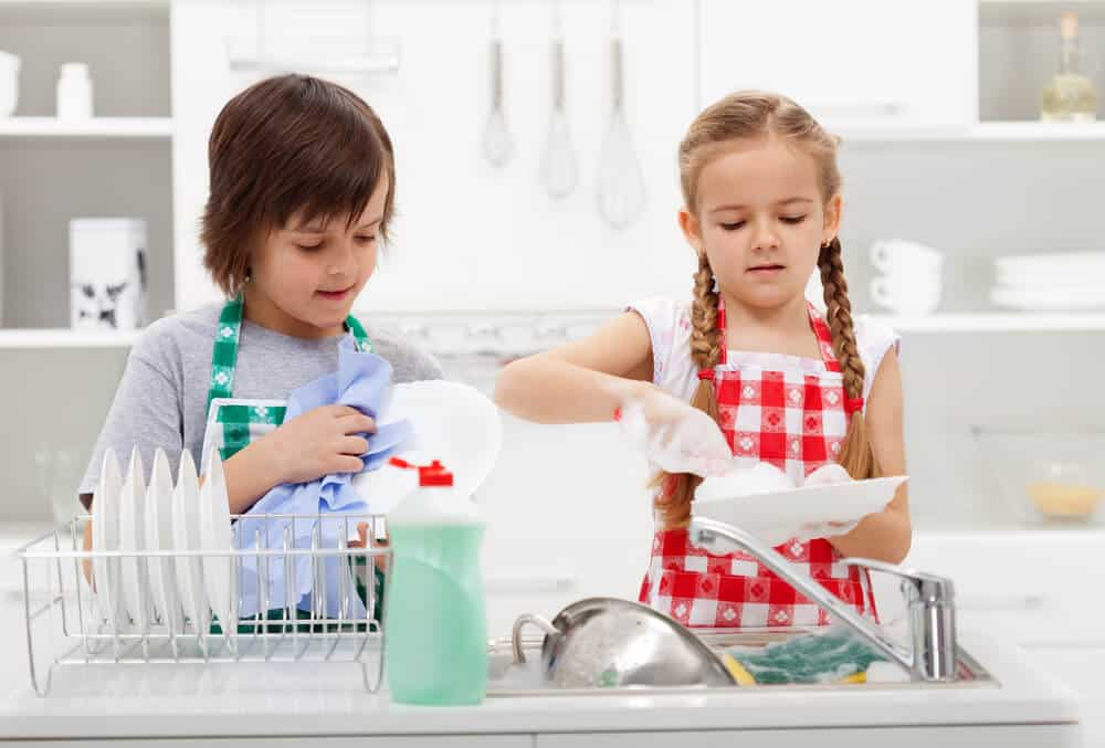 Siblings cleaning dishes
