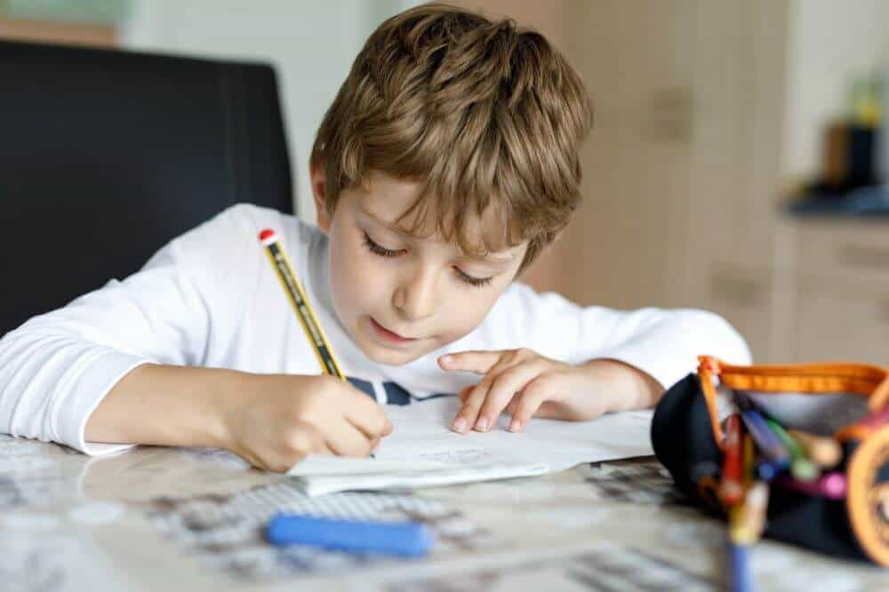Young boy working on school work at home
