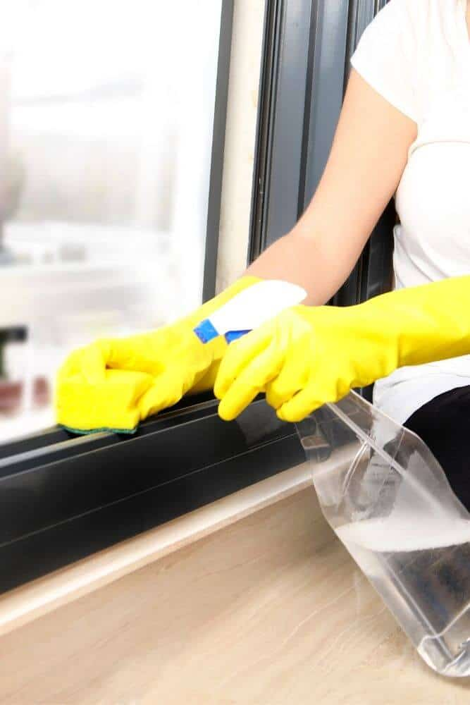 Person cleaning window tracks with sponge