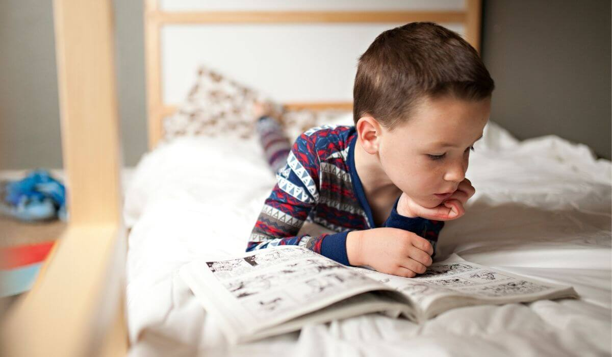 Boy reading comic book on bed