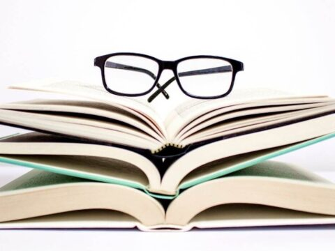 Books about decluttering stacked with reading glasses